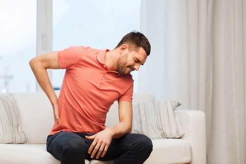 Man on couch with back pain properties of papaya seeds
