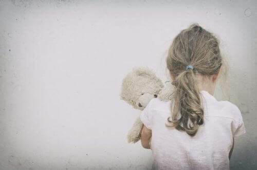 a lonely child hugging a teddy bear