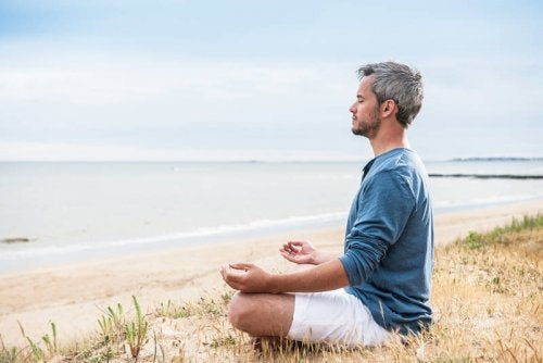 Man meditating on a calm beach how to be happier in life relax and have time for yourself