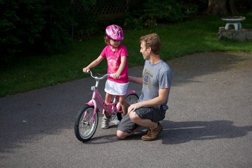 Father teaching daughter to ride a bike on driveway strong woman