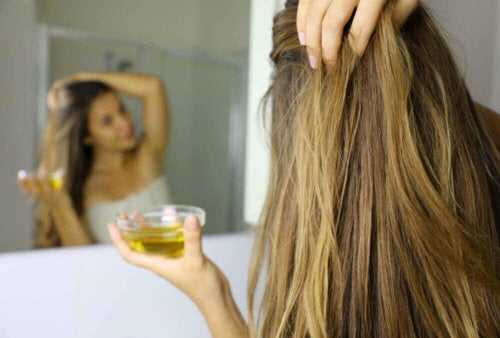 woman applhing oil to her hair looking in a mirror