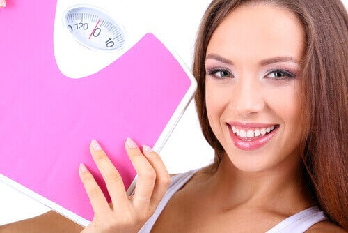 woman holding a pink, weight scale