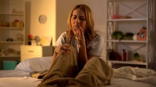 A woman eating junk food on the bed.