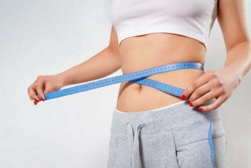 A woman measuring her waist.