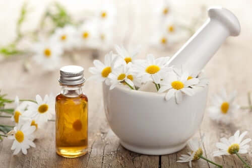 Some chamomile oil beside a mortar and pestol.
