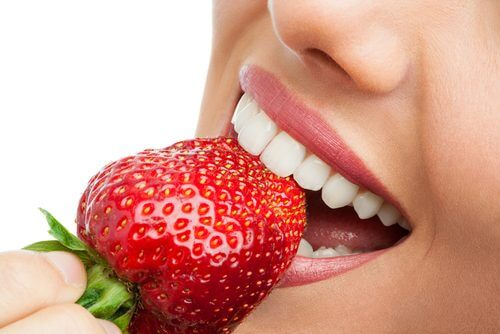 A woman eating a strawberry.