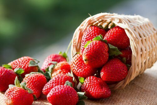Small basket full of small strawberries green in background arterial health