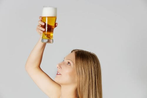 A woman holding a glass of beer.
