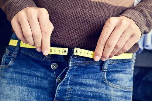 Person with tape measure at waist jeans diet affects your weight more with age