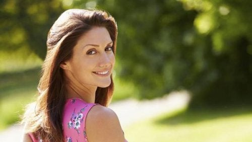 Woman in park looking back smiling diet affects your weight more as you age