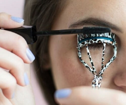 Woman curling her eyelashes with an eyelash curler harmful lush eyelashes