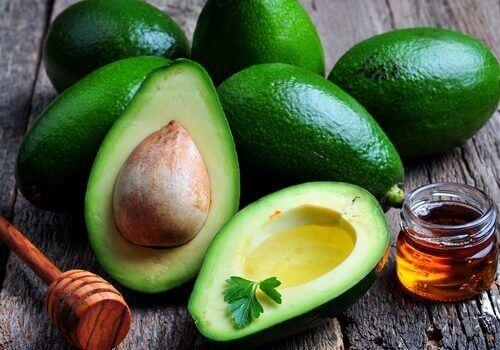 Avocado seed and whole avocado on table with honey jar