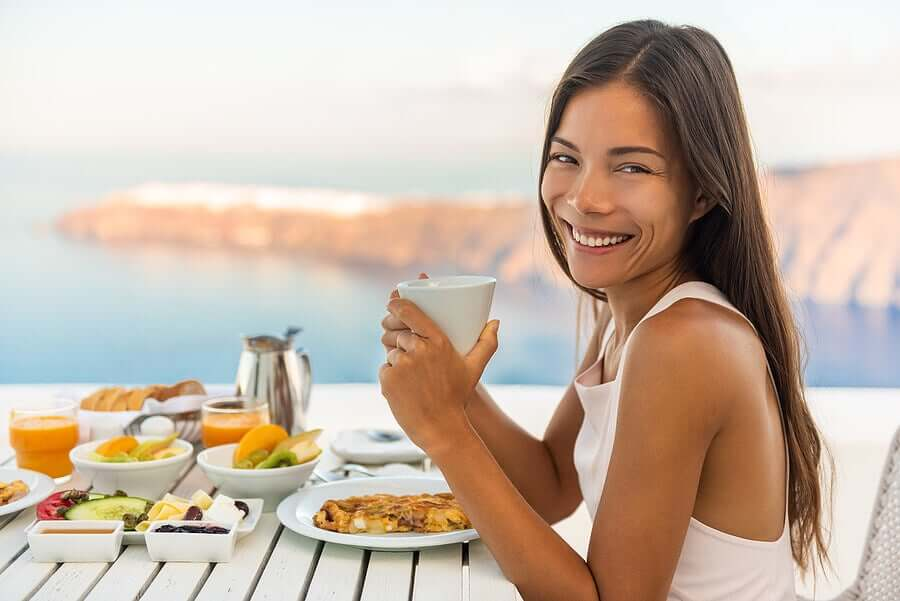 A woman eating a healthy meal at a table overlooking the ocean.