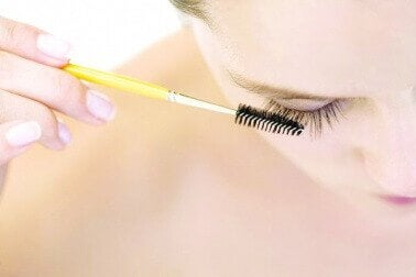 Woman brushing her eyelashes with a clean mascara wand lush eyelashes