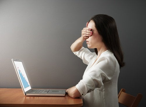 Woman covering her eyes in front of a computer