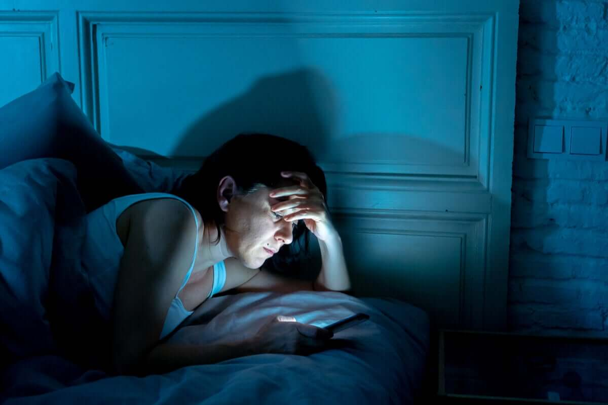 A woman looking at her phone at night.