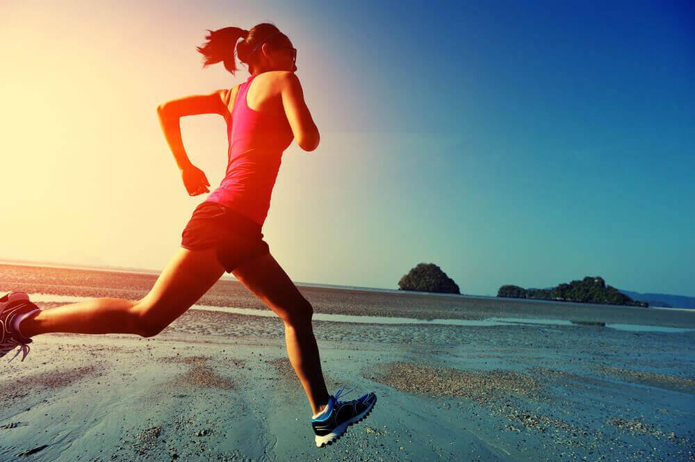 A woman running along the ocean shore.