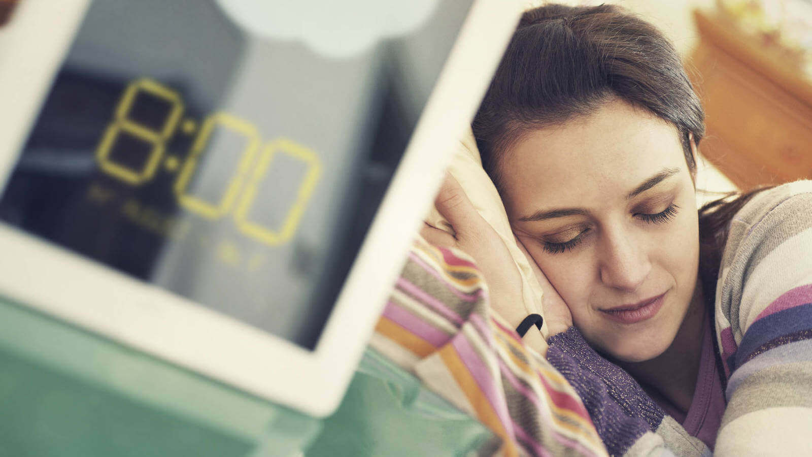 A closeup of a digital watch with a woman sleeping in the background.
