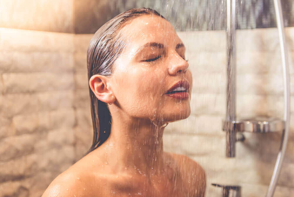 A woman rinsing her face in the shower.
