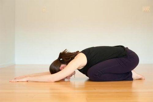 A woman doing the balasana pose.