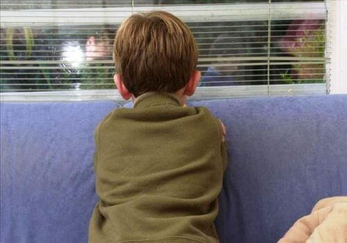 Young boy facing wall