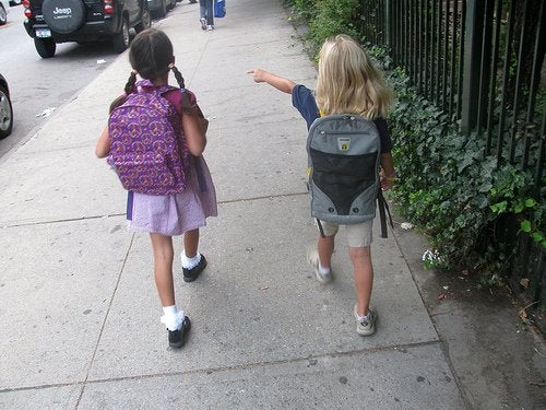 Two girls walking together on sidewalk identify a child abuser