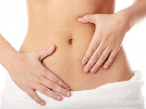 A woman holding her flat stomach.