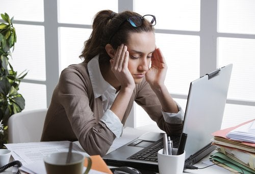 Woman with a headache in front of her computer
