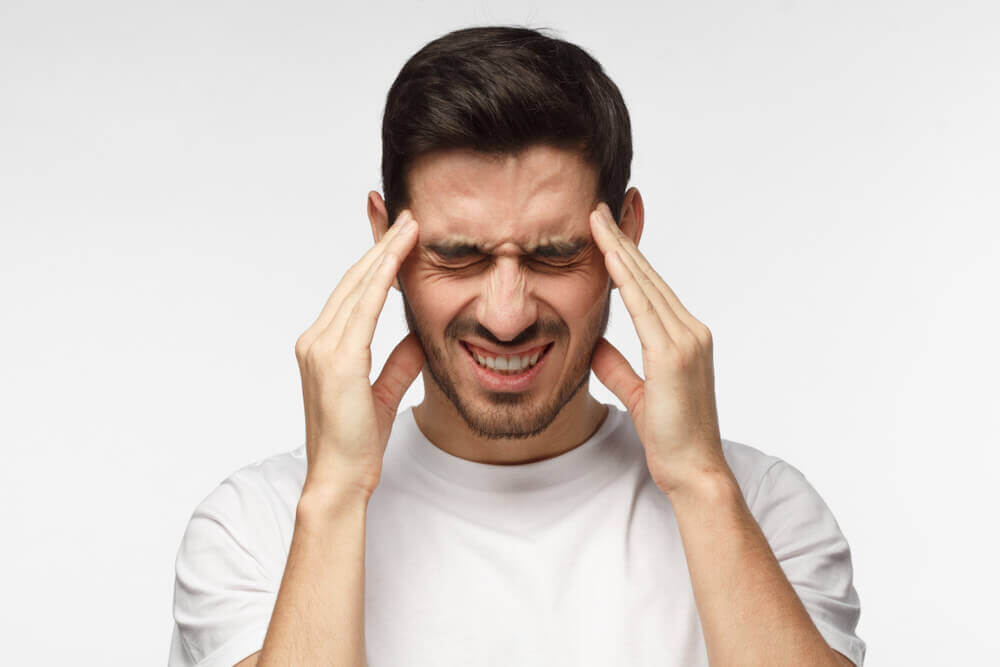A man with a headache presses his temples.