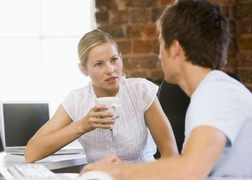 Blond woman and brunet man having coffee at work paid leave painful periods