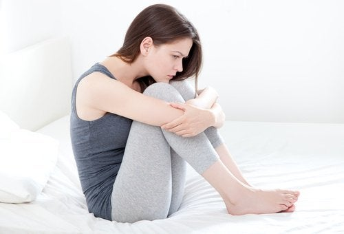 Painful periods woman sitting on bed folded at the waist dysmenorrhea