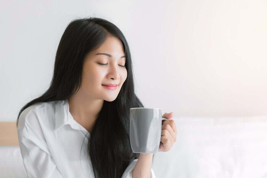 A woman holding a cup of tea with her eyes closed.