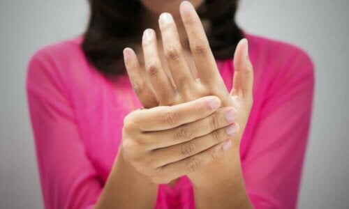A woman massaging her hand because of tingling skin.