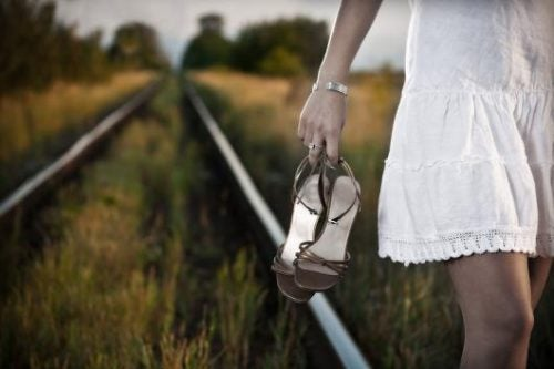 Woman walking along railroad track