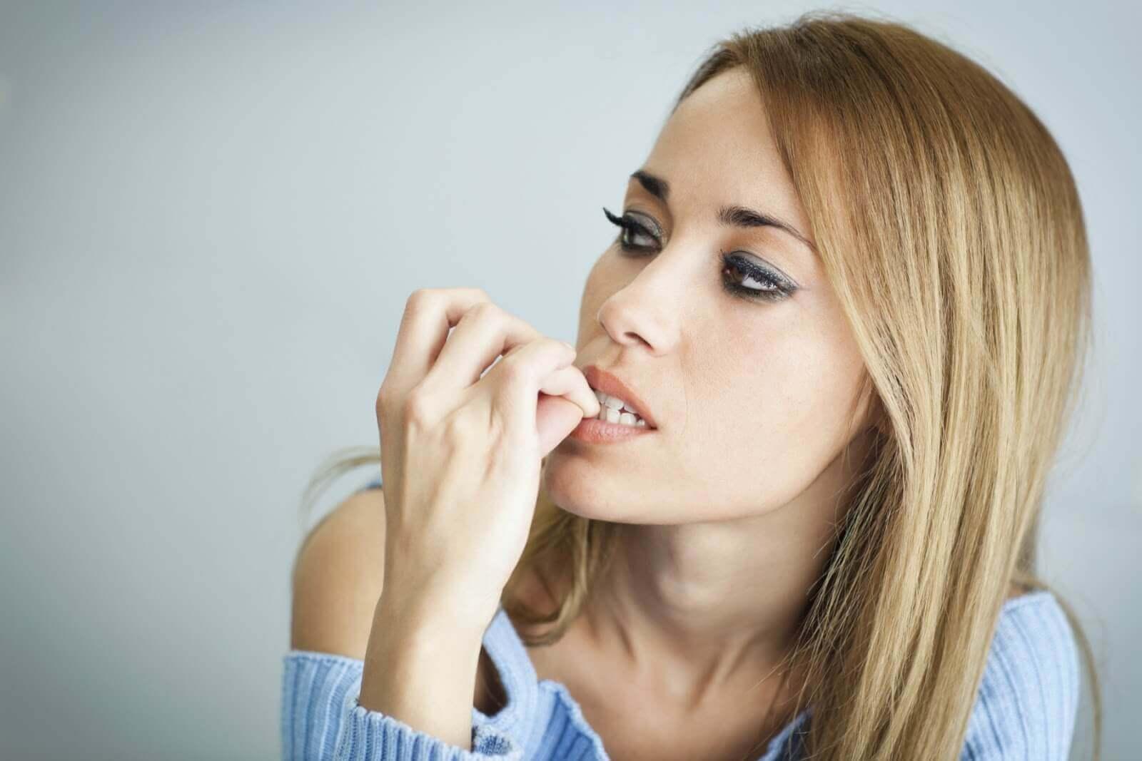 Anxious woman biting nails