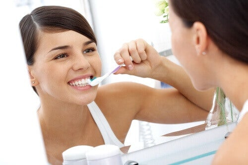 Woman brushing teeth in mirror dental plaque