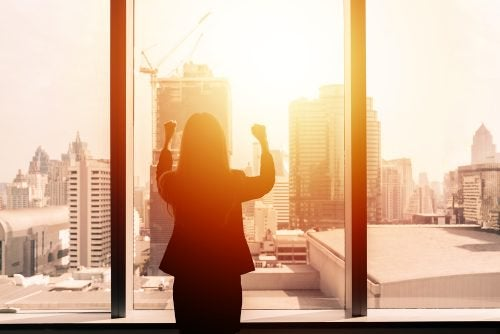 Woman watching sunrise from office