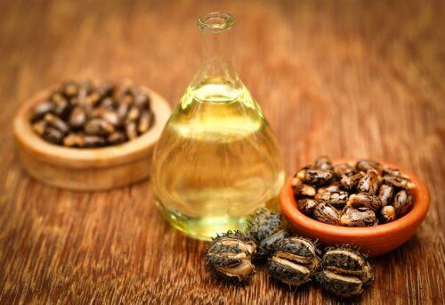 Castor oil vitamin e help strengthen nails bottle and bowls on wooden table