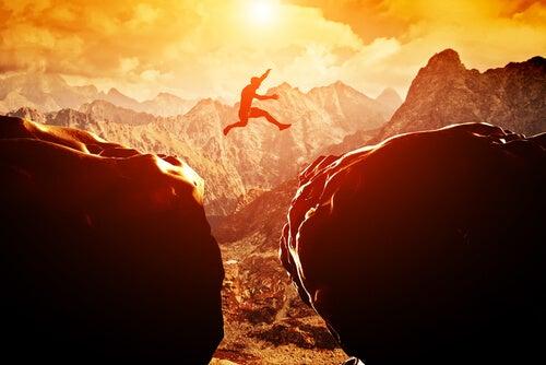 Man jumping between cliffs