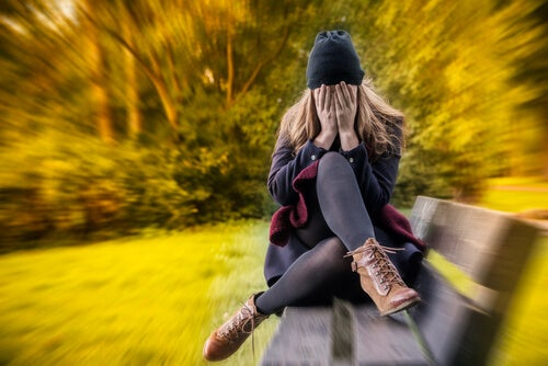 Woman with anxiety on bench in park