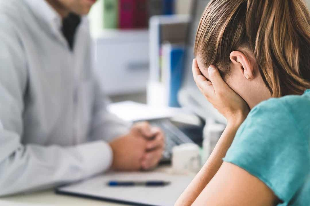 A female patient crying while talking with her doctor.