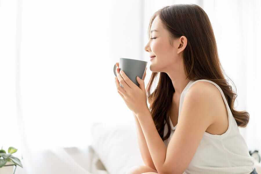 A woman drinking a cup of passionflower tea.