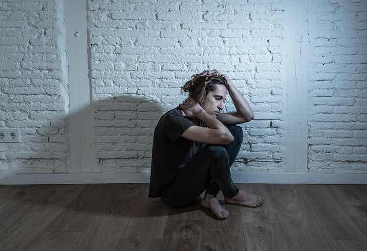 A young man sitting on the floor looking sad.