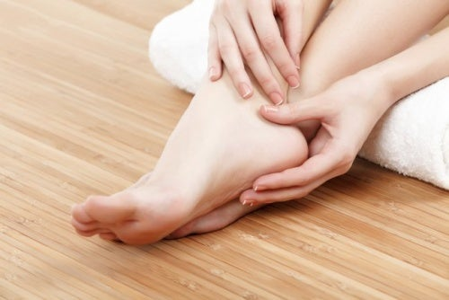 woman massages her ankle