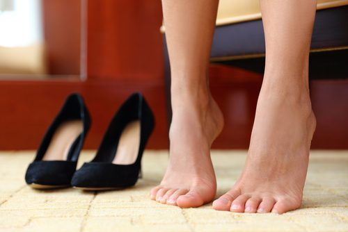 woman stretches her feet next to high heels