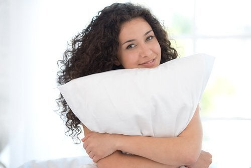 woman holding a pillow to reduce neck pain
