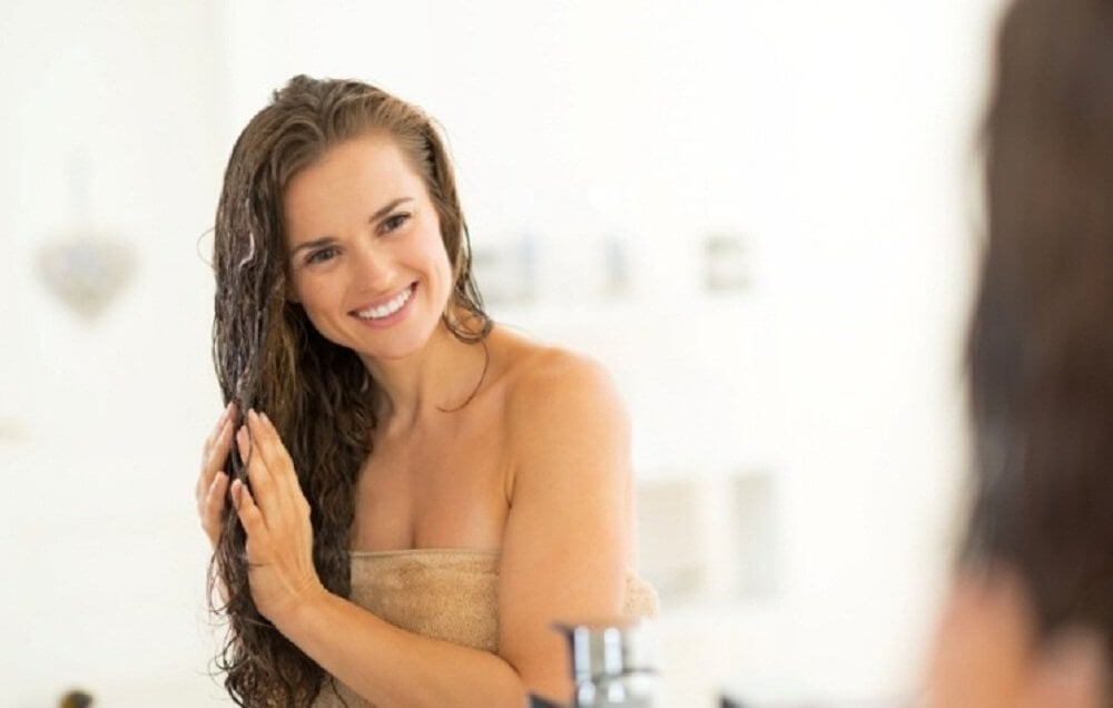 smiling woman washing her hair with apple cider vinegar beauty secrets