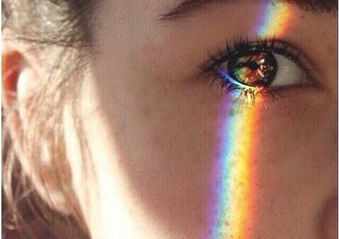 woman's eye with a rainbow over it