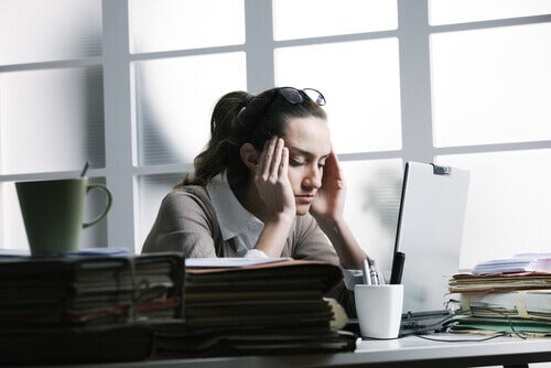 woman with stress headache in front of a computer at work