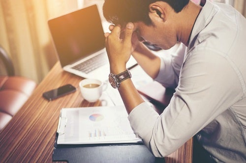 young man with headache at his desk in an office